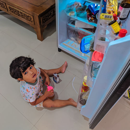 High angle view of girl in toy on floor at home