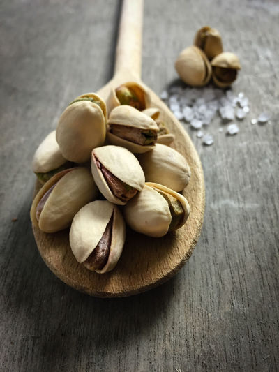Close-Up Of Pistachios On Wooden Spoon