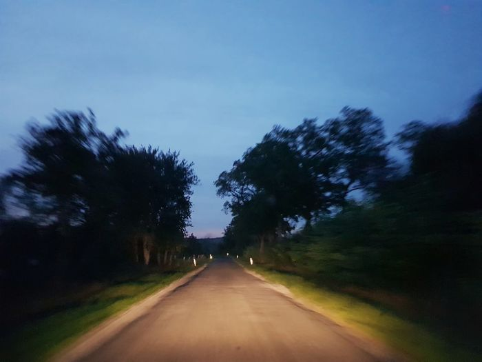 Road amidst trees against sky at dusk