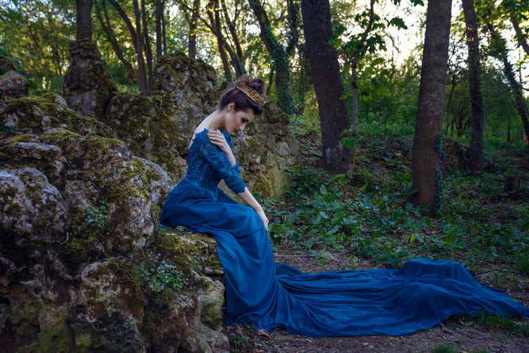 Side view of young woman wearing blue dress in forest