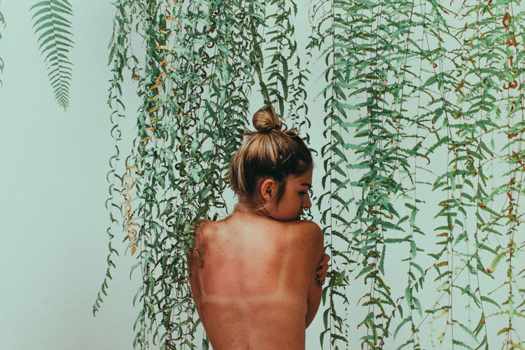 Rear view of shirtless woman standing against ivy wall