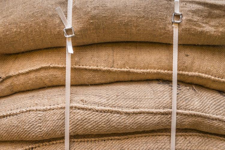 Full frame shot of stacked sacks at warehouse