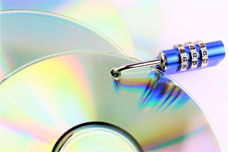 Close-Up Of Compact Discs With Padlock On Table