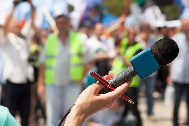 Cropped image of journalist holding microphone