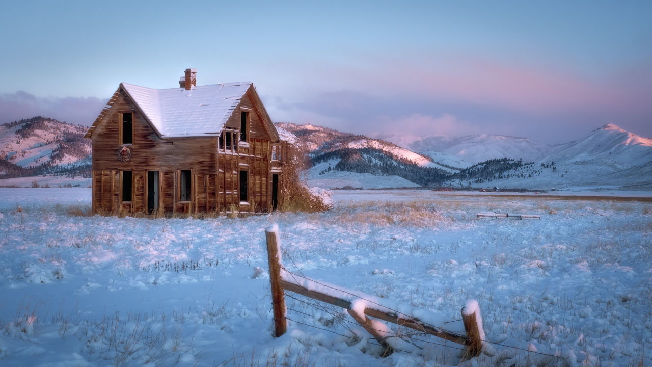 HOUSE ON SNOWCAPPED MOUNTAINS AGAINST SKY