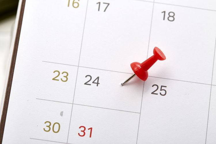 Close-up of push pin on calendar