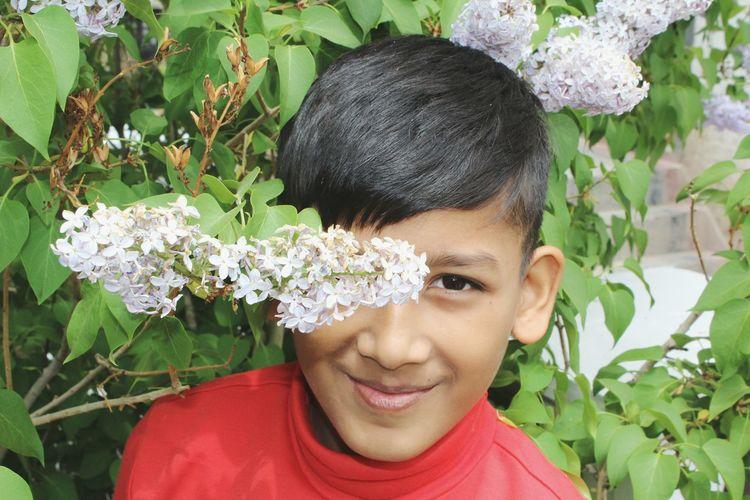 Portrait Of Boy Smiling Against Flowering Plant