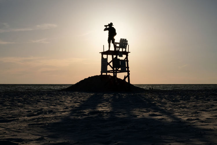 Silhouette man standing on lifeguard chair against sky during sunset