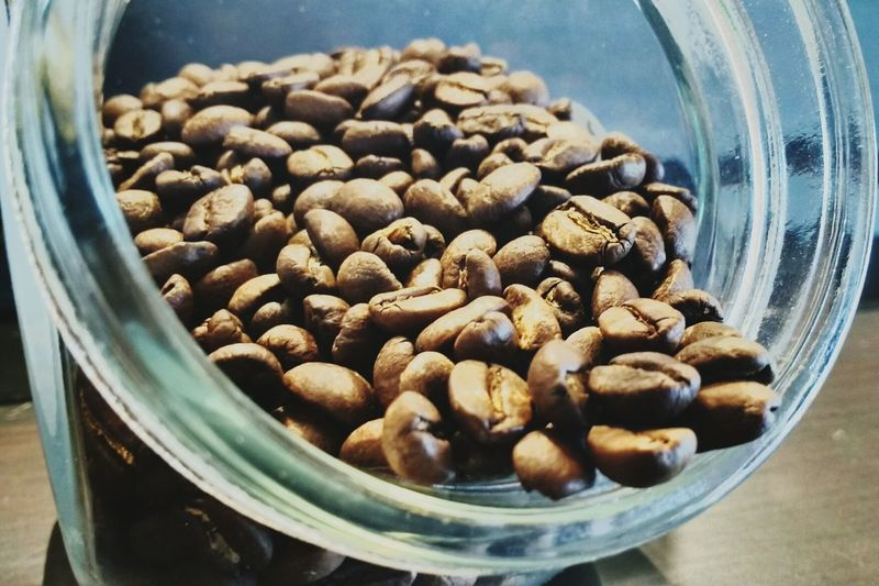 Close-up of roasted coffee beans in glass jar