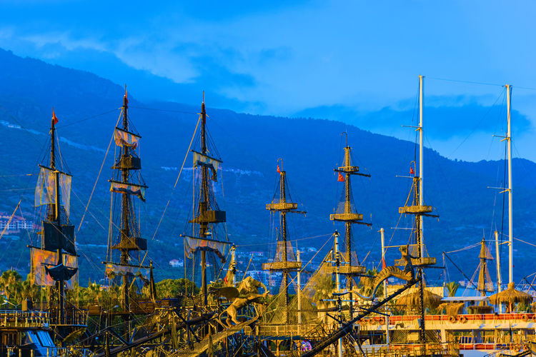 Old Ships Moored At Harbor By Mountains Against Sky At Dusk