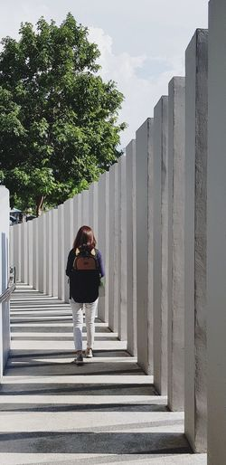 Rear view of woman standing on walkway