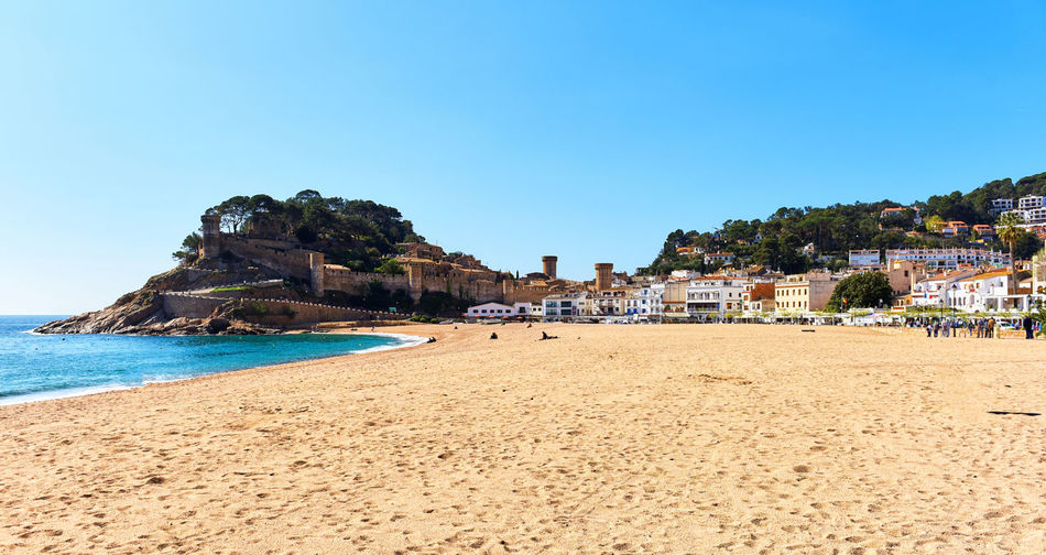 Scenic View Of Beach Against Clear Blue Sky At Tossa De Mar
