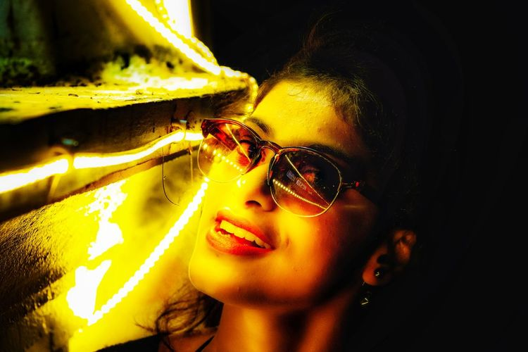 Close-Up Portrait Of Young Woman Wearing Sunglasses By Illuminated Lights