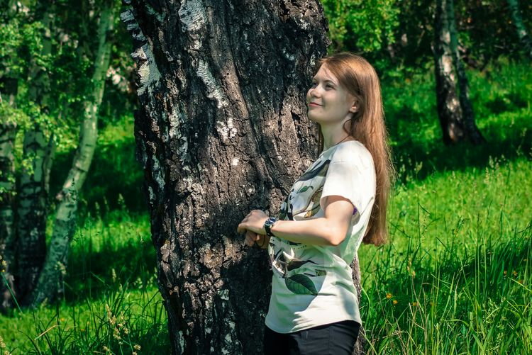 Smiling Woman Standing By Tree On Grassy Field