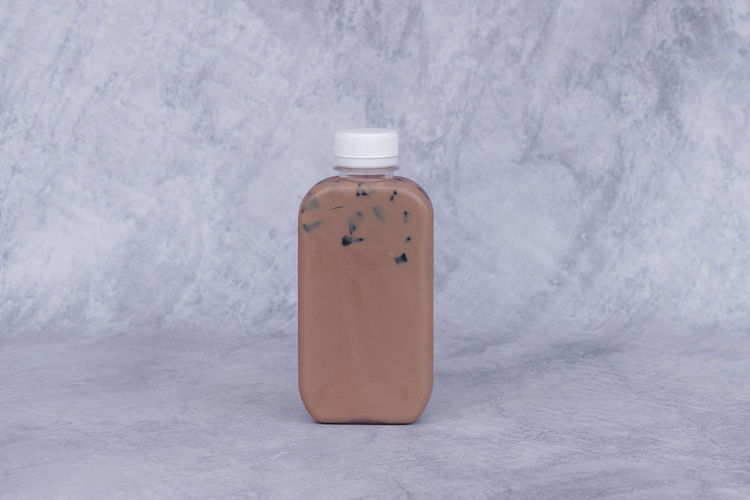 Close-up of bottle on table against wall