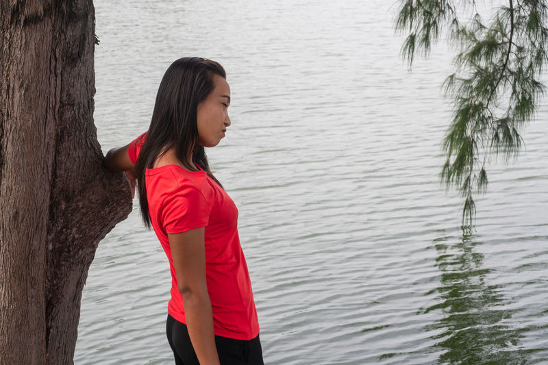 Beautiful young woman standing by tree trunk in lake