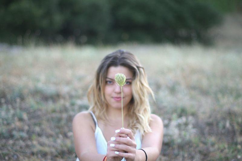 Portrait of young woman holding flower bud on field