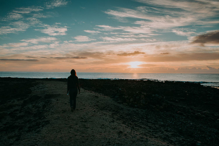 Rear view of woman walking towards sea against sky during sunset