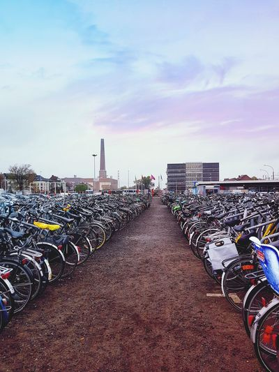 Bicycles parked in row against sky