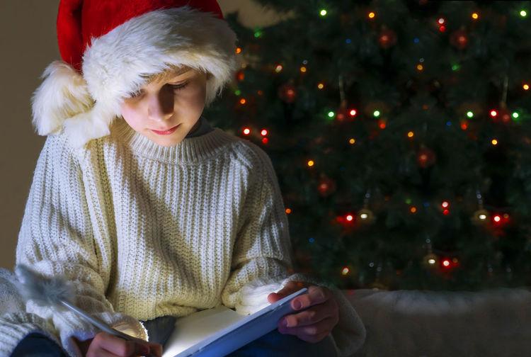 Girl looking at illuminated christmas tree