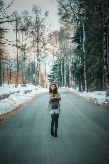 Portrait of young woman standing on road amidst trees during winter