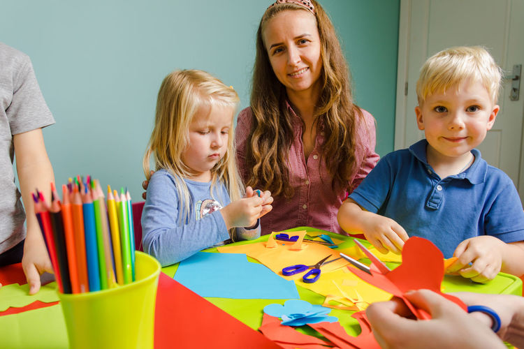 Portrait of mother and kids doing craft at home