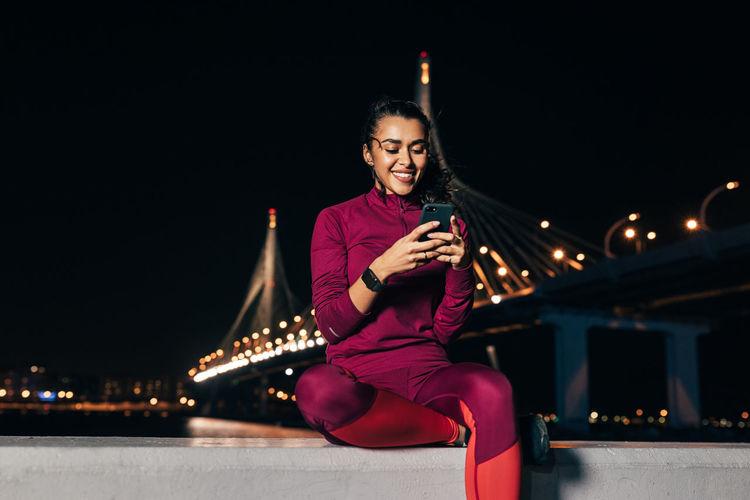 Woman using smart phone sitting on retaining wall