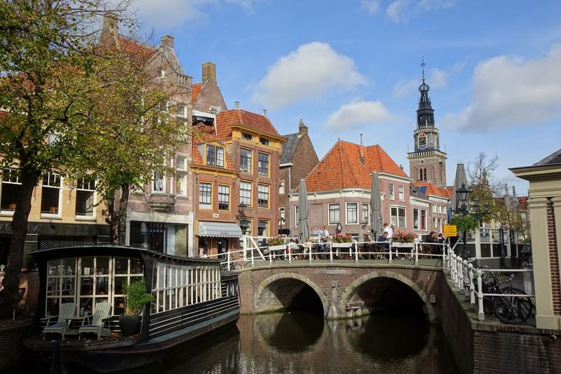 Arch Bridge Over Canal Against Buildings In City