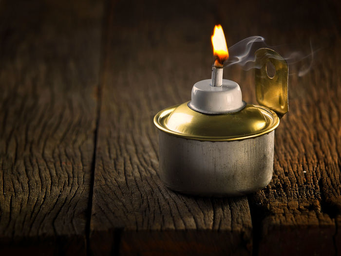 Close-up of burning candle on table