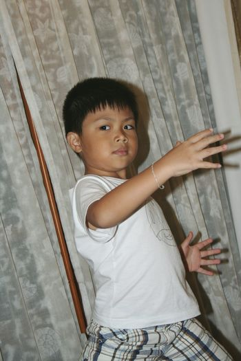 Portrait of boy posing against curtain at home