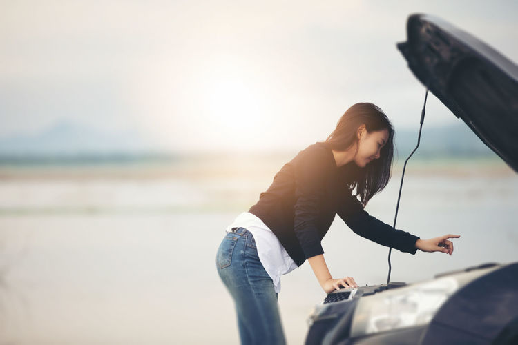 Side View Of Woman Looking At Car Engine On Road