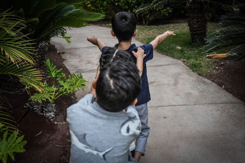 Rear view of playful children on footpath at park