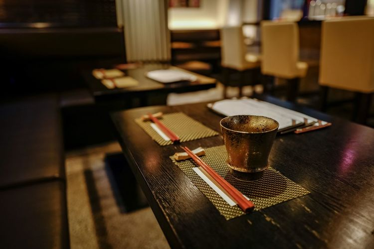 High angle view of drinking glass and chopsticks on place mat over table