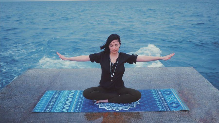 Full Length Of Woman Performing Yoga Against Sea