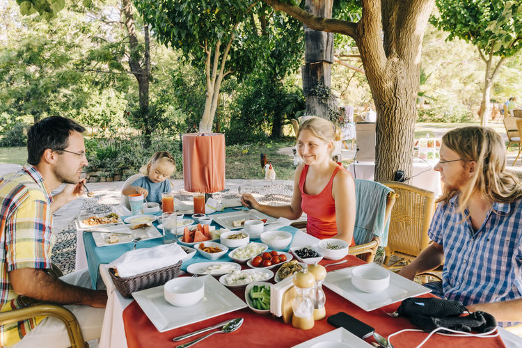 Family having meal at table in yard