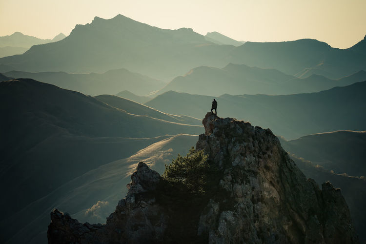 Silhouette person on rock by mountains against sky