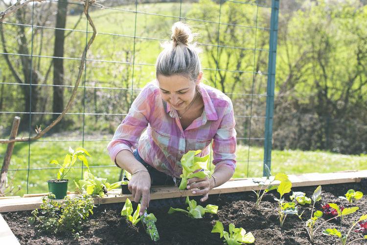 Smiling Woman Gardening In Yard