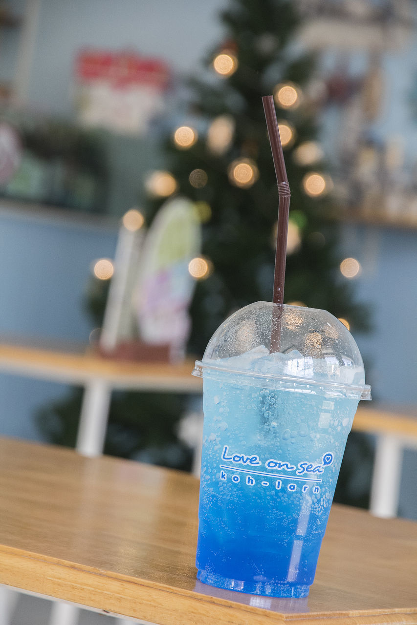 table, drink, food and drink, refreshment, focus on foreground, drinking straw, straw, close-up, indoors, freshness, glass, no people, household equipment, still life, wood - material, blue, food, drinking glass, glass - material