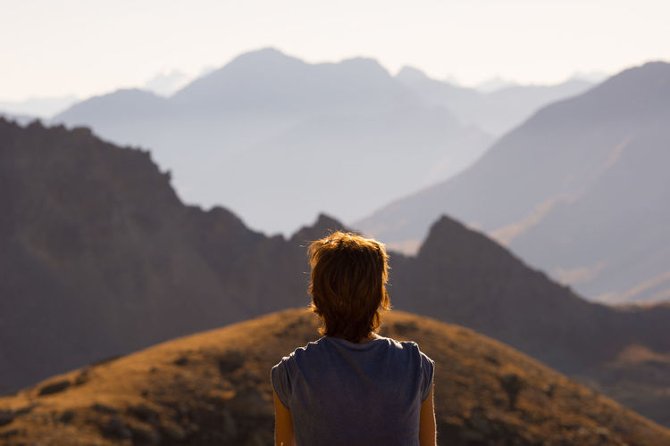 Rear view of woman standing on mountain against sky