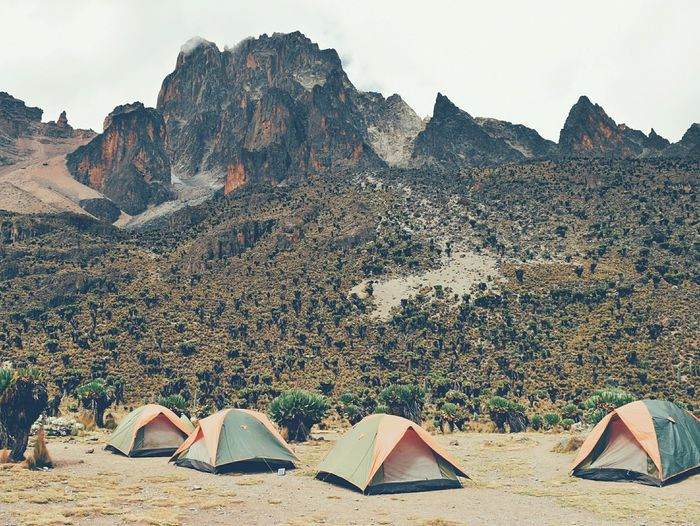 Tents against rocky mountains