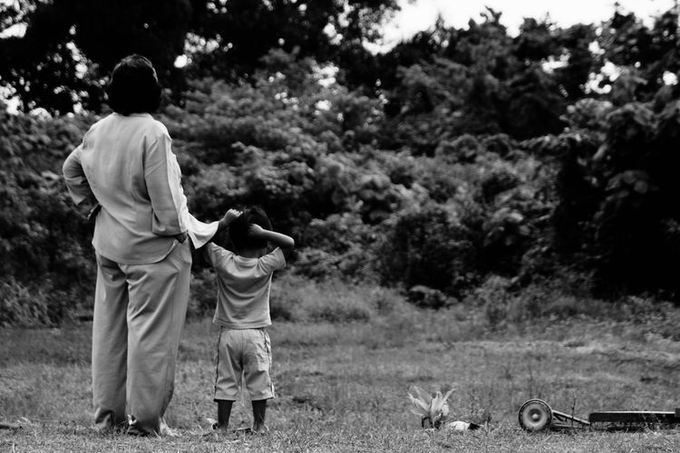 Rear view of woman and boy in park