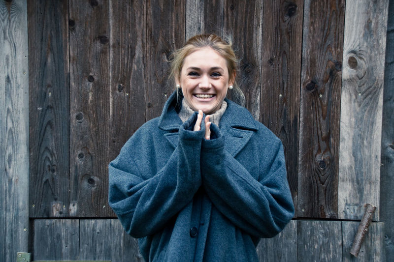 Portrait Of Smiling Young Woman Wearing Warm Clothing Standing Against Wooden Wall