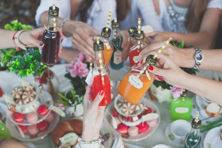 Cropped image of hands cheersing colorful drinks over macarons at a party