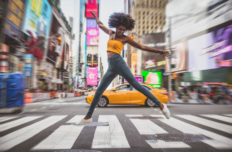 Full length of excited young woman dancing on zebra crossing in city