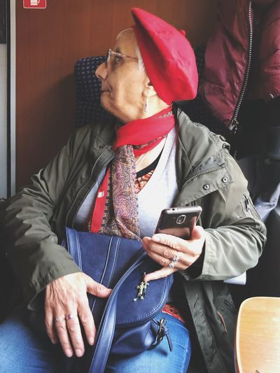 Senior woman in warm clothes holding mobile phone
