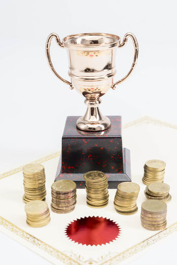 Trophy Cup and coins and blank certificate on white background Still Life Indoors  Coin Success Studio Shot Wealth Finance No People Stack Achievement Business Close-up White Background Currency Investment Savings Table Winning Large Group Of Objects Metal Silver Colored