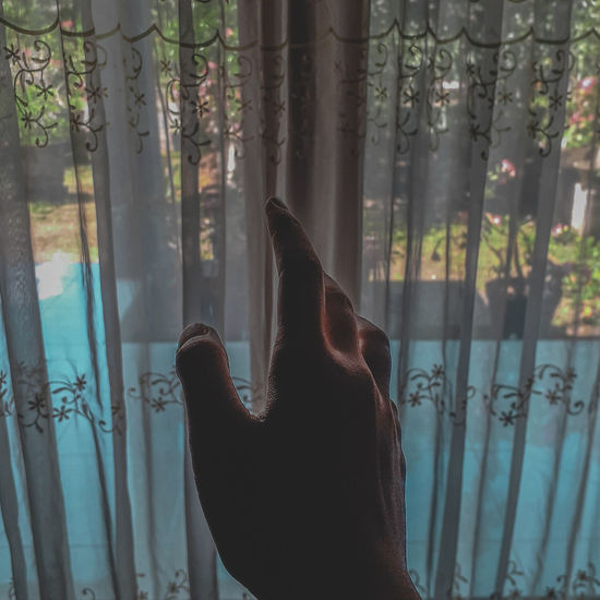 Cropped hand of woman touching curtain