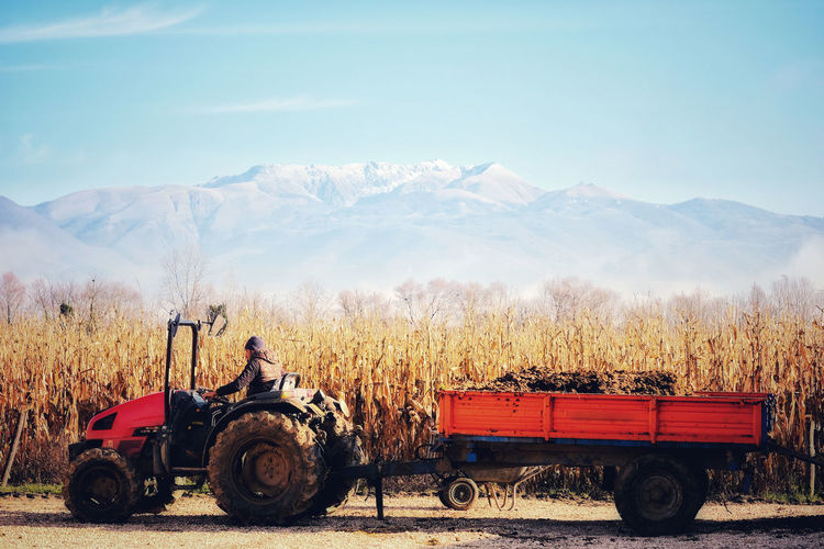 Man working with a tractor on a corn field against sky