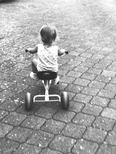 Rear View Of Girl Riding Tricycle On Footpath