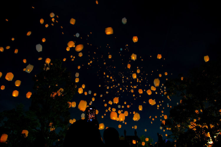 Low angle view of illuminated paper lanterns flying in sky at night